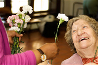 Someone giving an elderly woman a flower photo